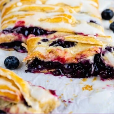 Blueberry danish with slices cut off and recipe title on the bottom of photo