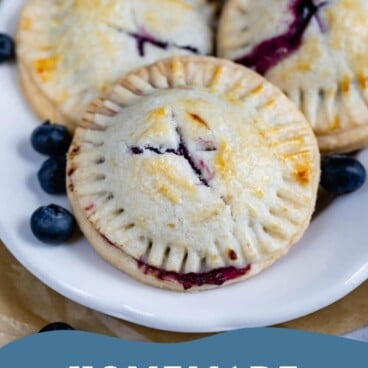 Three blueberry hand pies on a plate with recipe title on bottom of photo