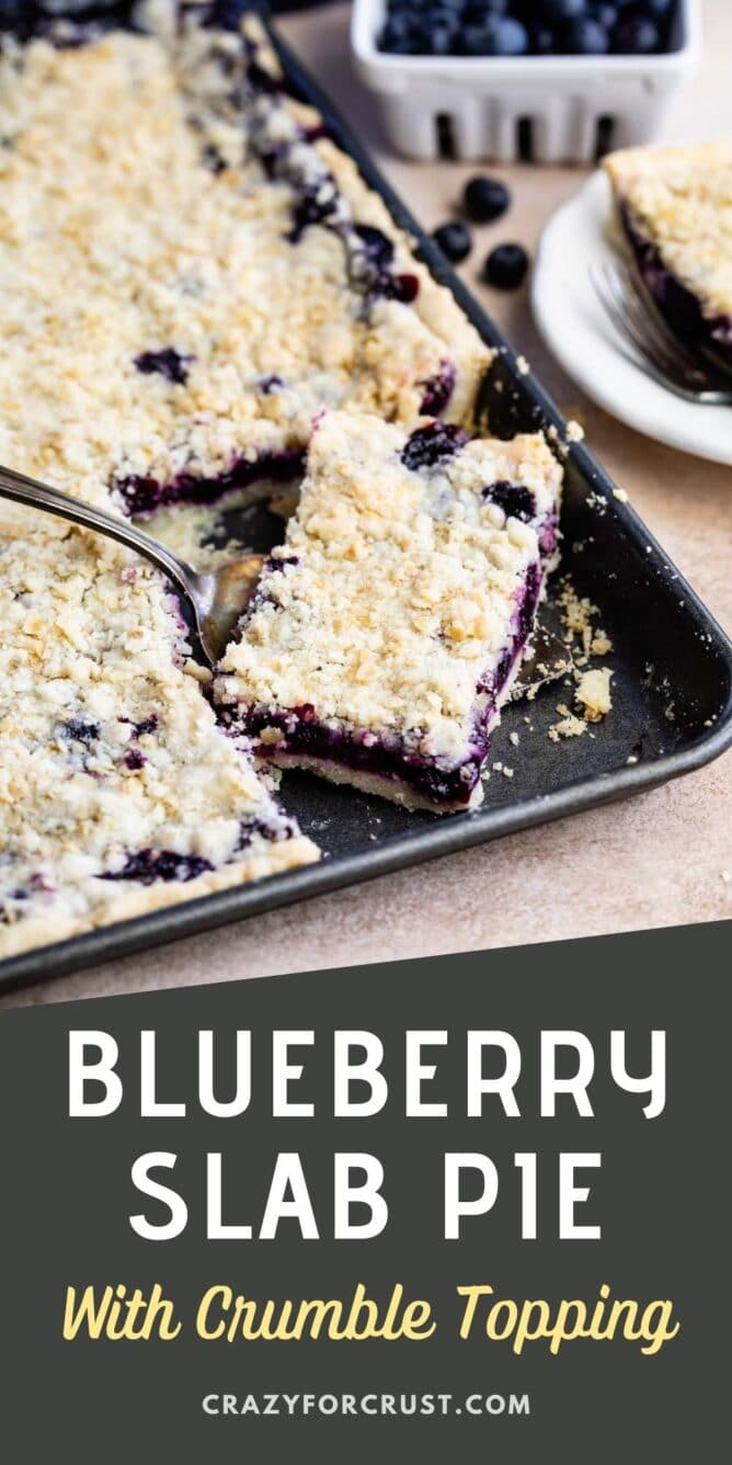 Blueberry slab pie in sheet pan with corner piece being scooped out with a serving spoon and recipe title on bottom of photo