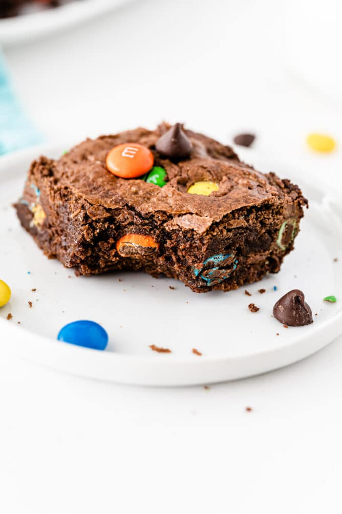 One M&M brownie on a white plate with a bite missing from the corner