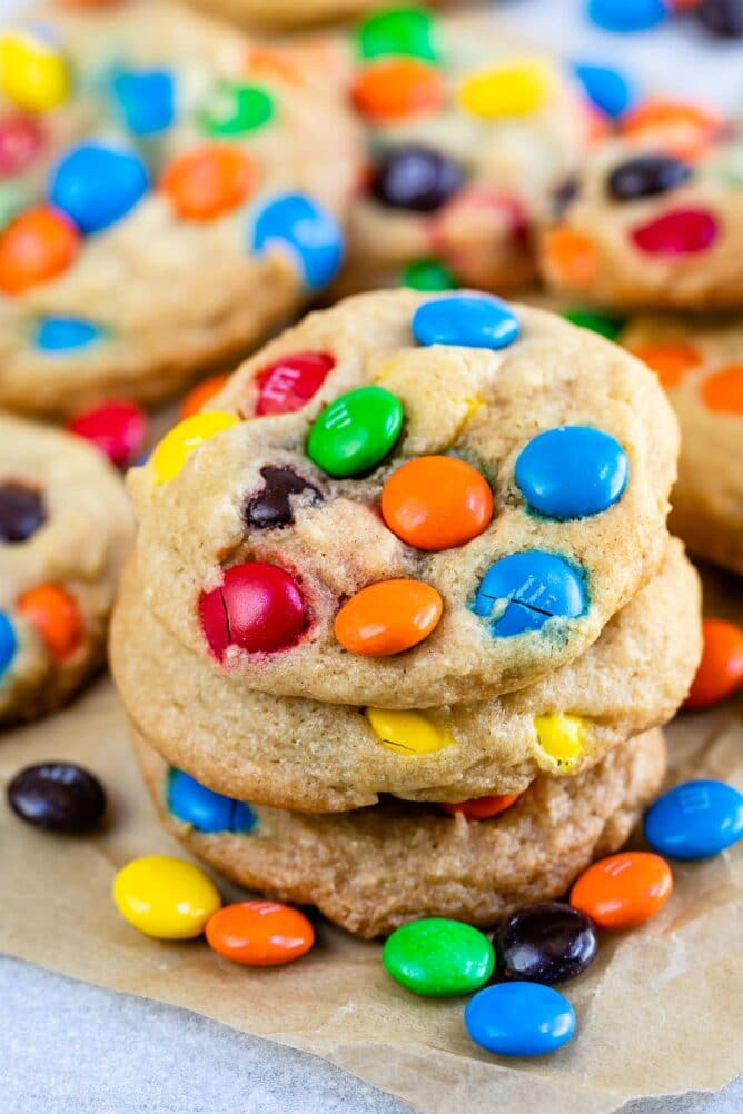 Stack of chocolate chip M&M cookies on parchment paper