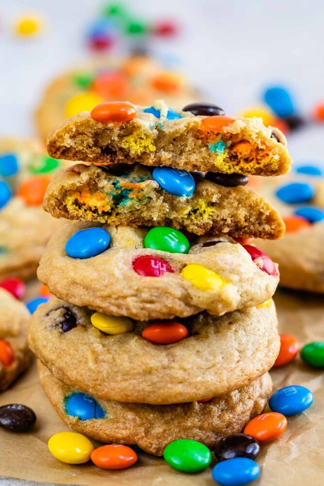 Stack of chocolate chip M&M cookies on parchment paper with top cookie cut in half to show M&Ms on the inside