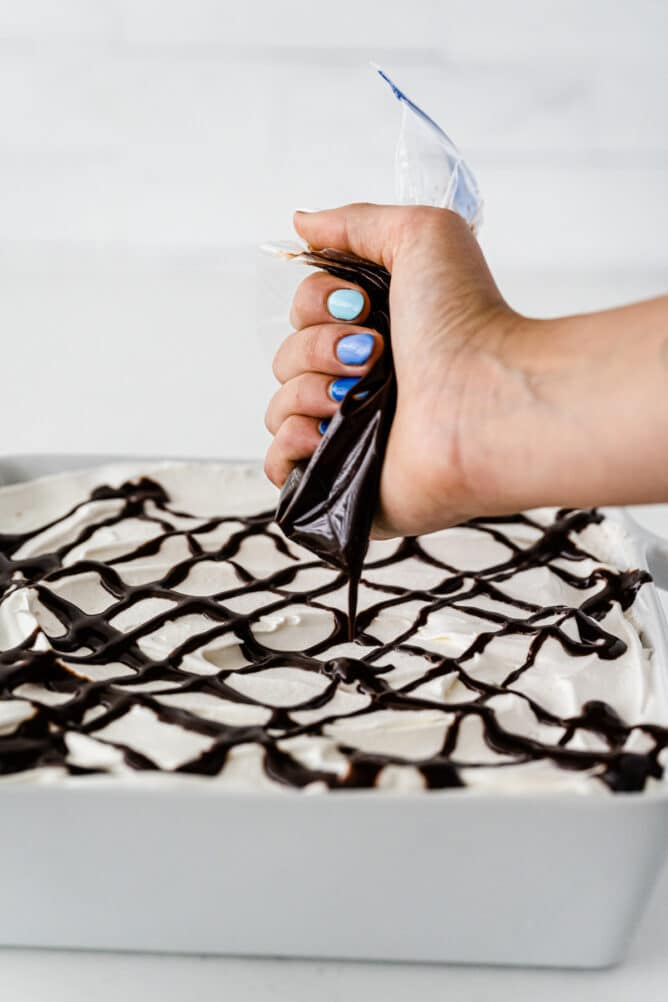 hand drizzling chocolate sauce on mocha mud pie