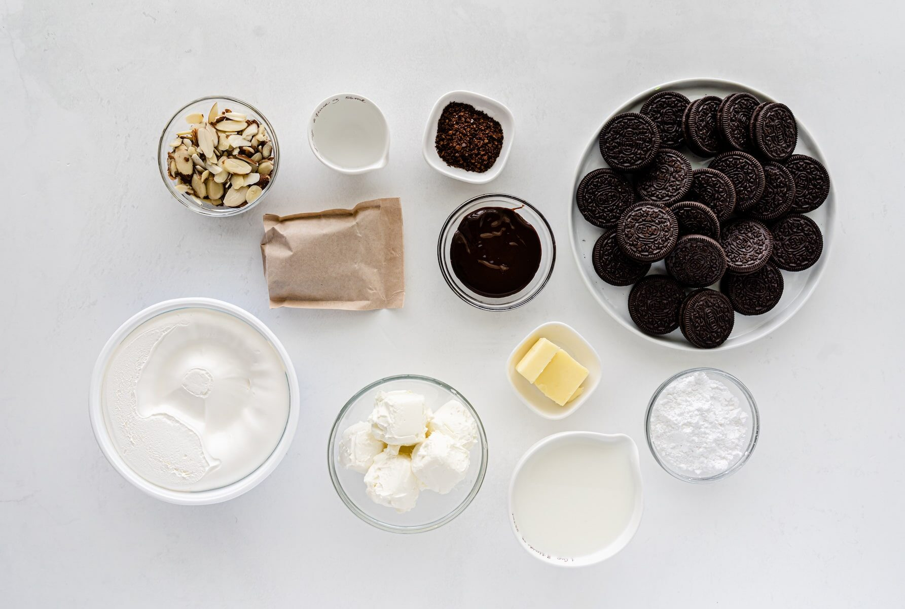ingredients in mocha mud pie - bowls of Oreos, almonds, whipped cream powdered sugar and butter