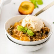 Peach crisp in a white bowl topped with vanilla ice cream and mint leaves