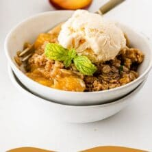 Bowl of peach crisp topped with vanilla ice cream and recipe title on bottom of photo