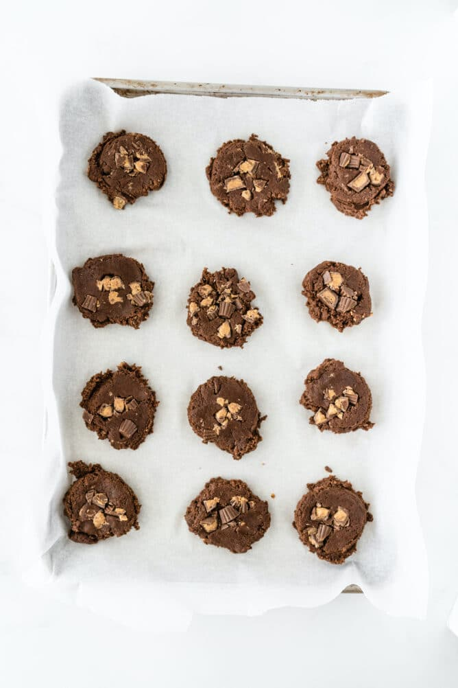 Overhead shot of soft chocolate peanut butter cup cookie dough set on a baking sheet ready to bake