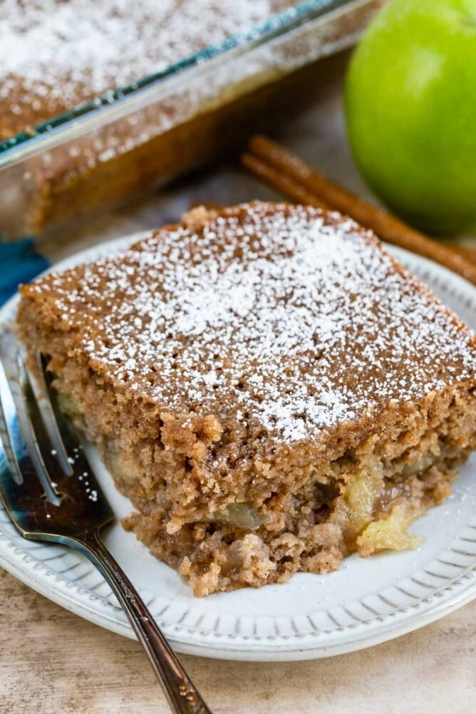 Slice of apple pie cake topped with powdered sugar