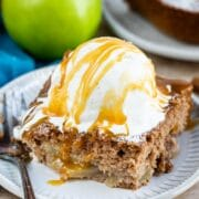 Slice of apple pie cake topped with vanilla ice cream and caramel sauce