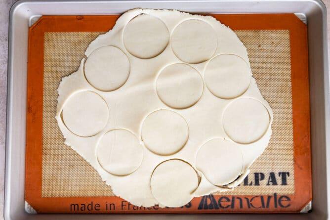 Overhead shot of pie crust circles cut into pie crust on a baking sheet