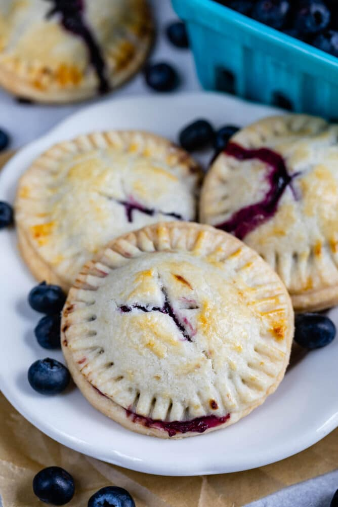Three blueberry hand pies on a white plate with blueberries behind it