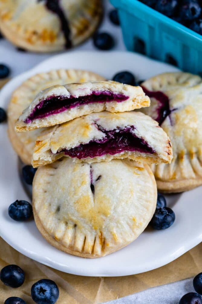 Blueberry hand pies on a plate with one split in half to show blueberry filling