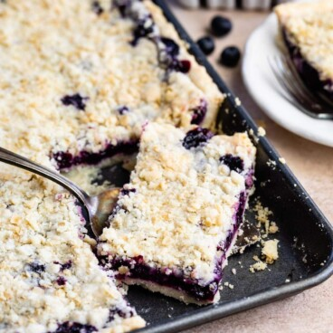 Blueberry slab pie in sheet pan with corner piece being scooped out with a serving spoon
