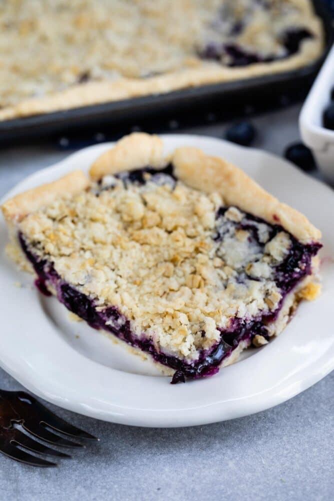 Corner piece of blueberry slab pie on a white dessert plate