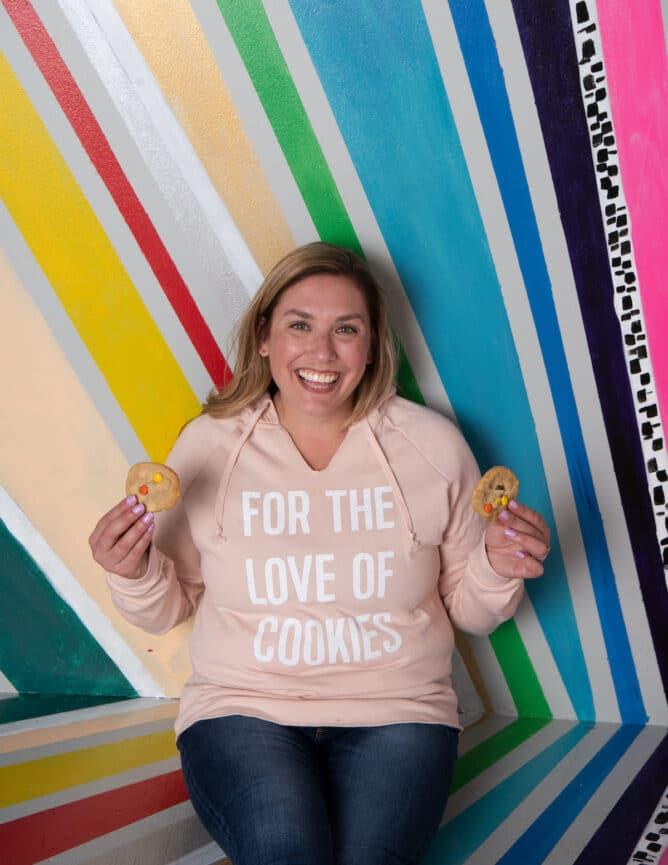 woman in sweatshirt holding cookies