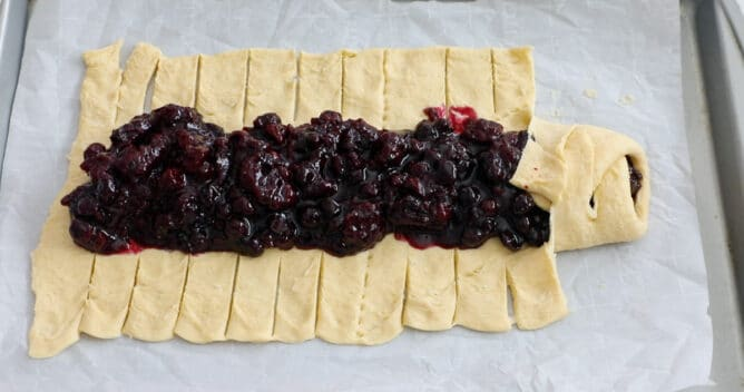crescent roll dough with filling down the center on cookie sheet