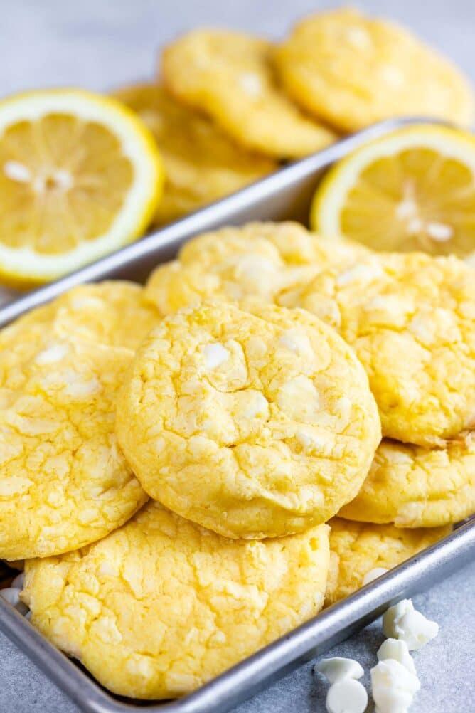 Baking pan full of lemon white chocolate cake mix cookies, white chocolate chips and lemon slices