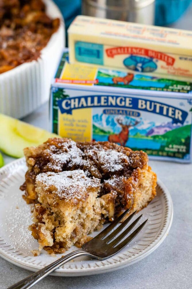 Apple Coffee Cake slice on white plate with butter box behind