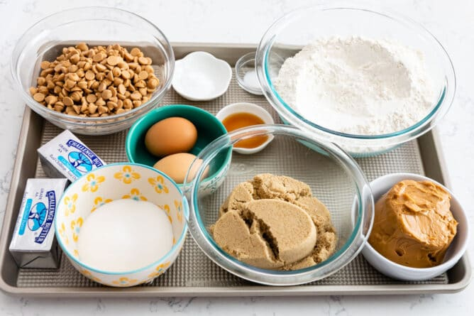 All ingredients needed to make XL bakery style peanut butter cookies measured out on a sheet pan