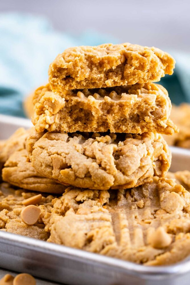 Stack of XL bakery style peanut butter cookies with top cookie split in half to show inside