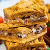 Three pumpkin gooey bars stacked on top of eachother with a pumpkin candy next to them