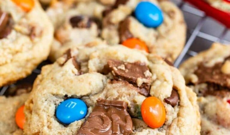 Close up shot of candy bar cookies on a metal cooling rack with recipe title on top of image