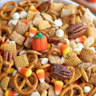 Large bowl of pumpkin spice chex mix with recipe title on top of image