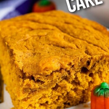Slice of pumpkin snake cake on a plate next to pumpkin candies and recipe title on top of image