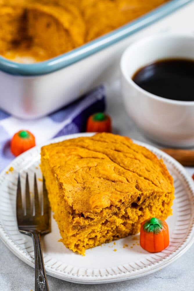 Overhead view of corner slice of pumpkin snack cake on a plate with a fork