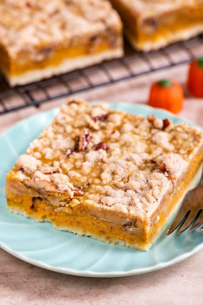 Pumpkin pie bar cut into a square on a light blue plate