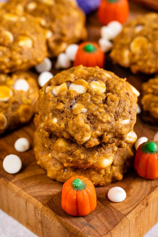 Pumpkin oatmeal cookies on a cutting board with pumpkin candies and white chocolate chips
