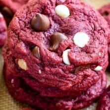 Stack of red velvet cookies with more cookies around it and recipe title on top of image