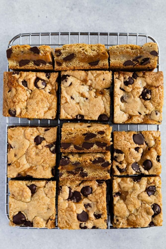Overhead shot of caramel chocolate chip cookie bars cut into squares on wire cooling rack