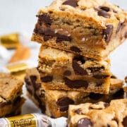 Stack of caramel chocolate chip cookie bars with candys around them