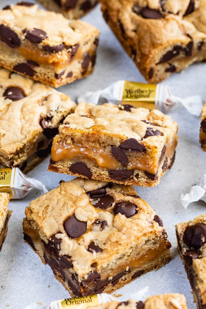 Close up shot of two caramel chocolate chip cookie bar squares with more cookie bars and candy around them