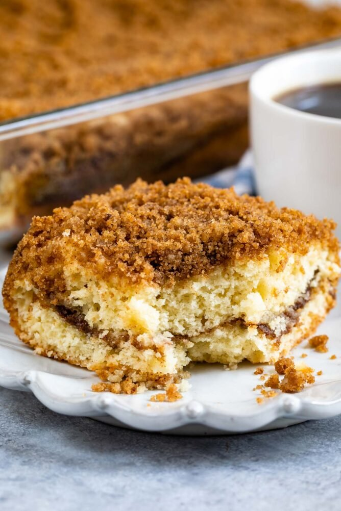 One piece of streusel coffee cake on a plate with corner piece missing
