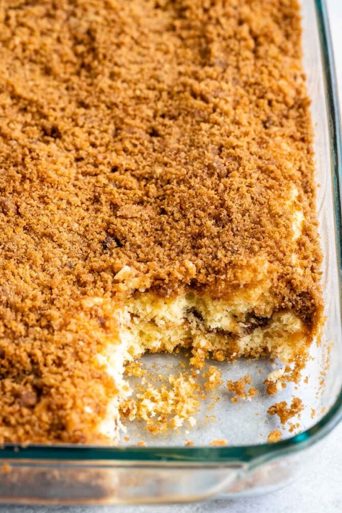 Overhead shot of streusel coffee cake in baking pan with corner piece missing