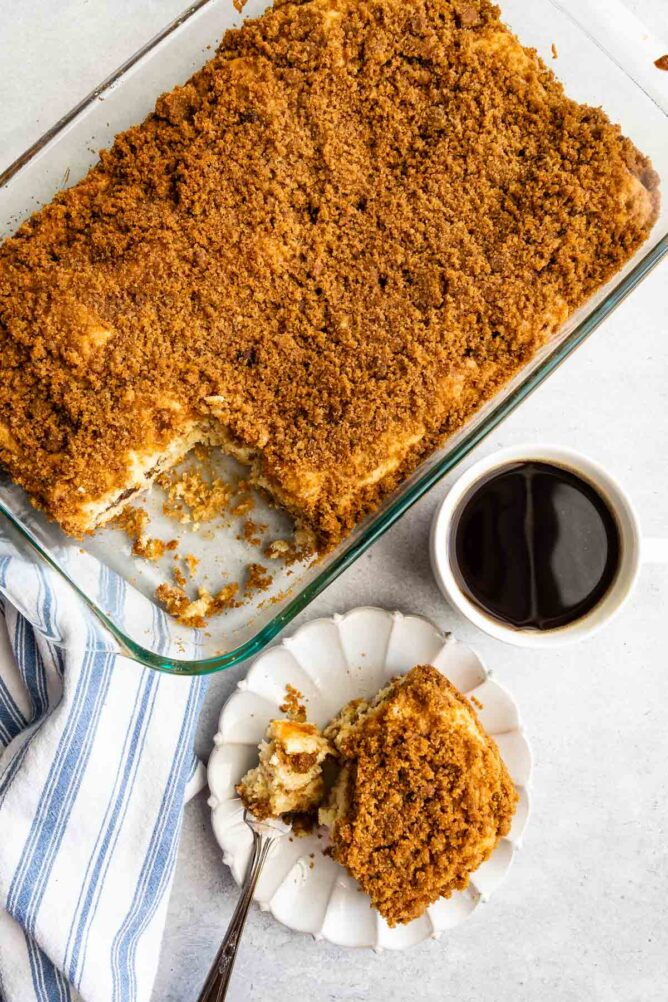 Overhead shot of streusel coffee cake in pan with one slice on a plate next to a cup of coffee