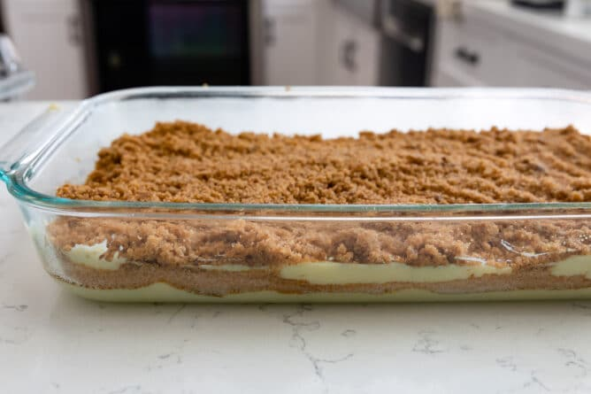 Side view of streusel coffee cake in a clear baking dish