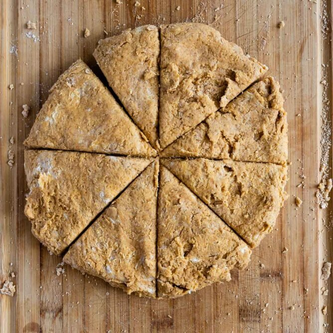 Overhead shot of pumpkin scones cut into triangles on a wooden cutting board