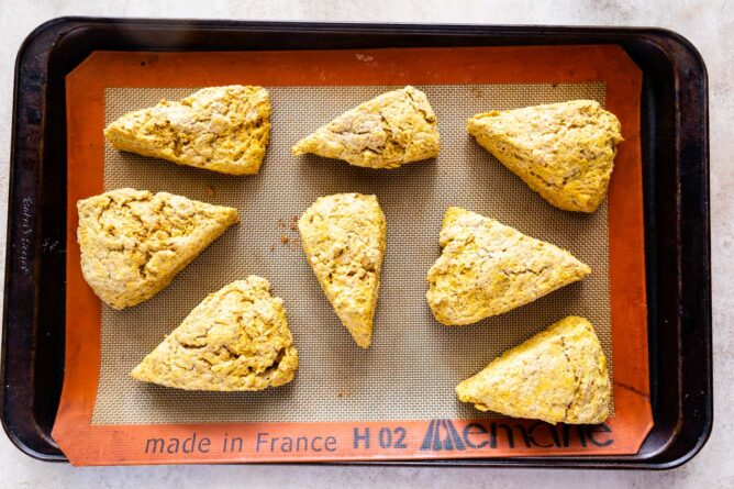 Overhead shot of pumpkin scones on a baking sheet with silicon mat