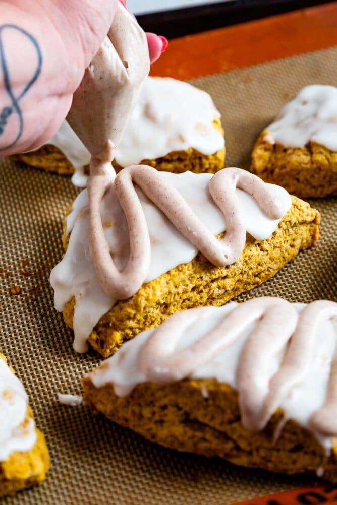 Close up shot of pumpkin scones being iced