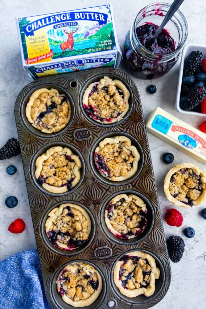 Overhead shot of mini berry pies in muffin tin with ingredients all around it
