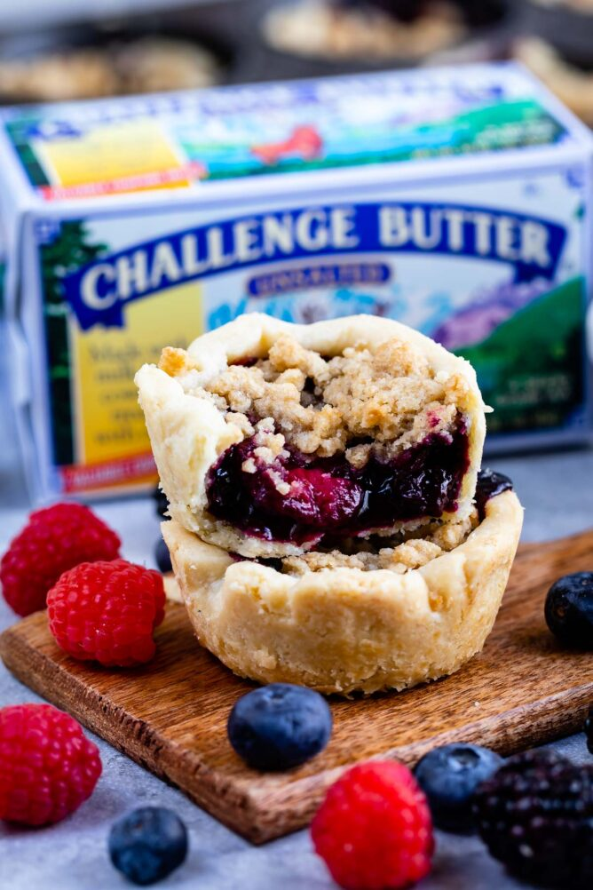 Two mini berry pies stacked on top of eachother with butter and fruit in the background