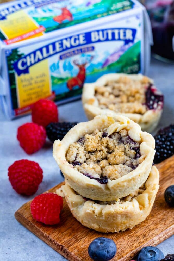 Mini berry pies with butter and fruit in the background