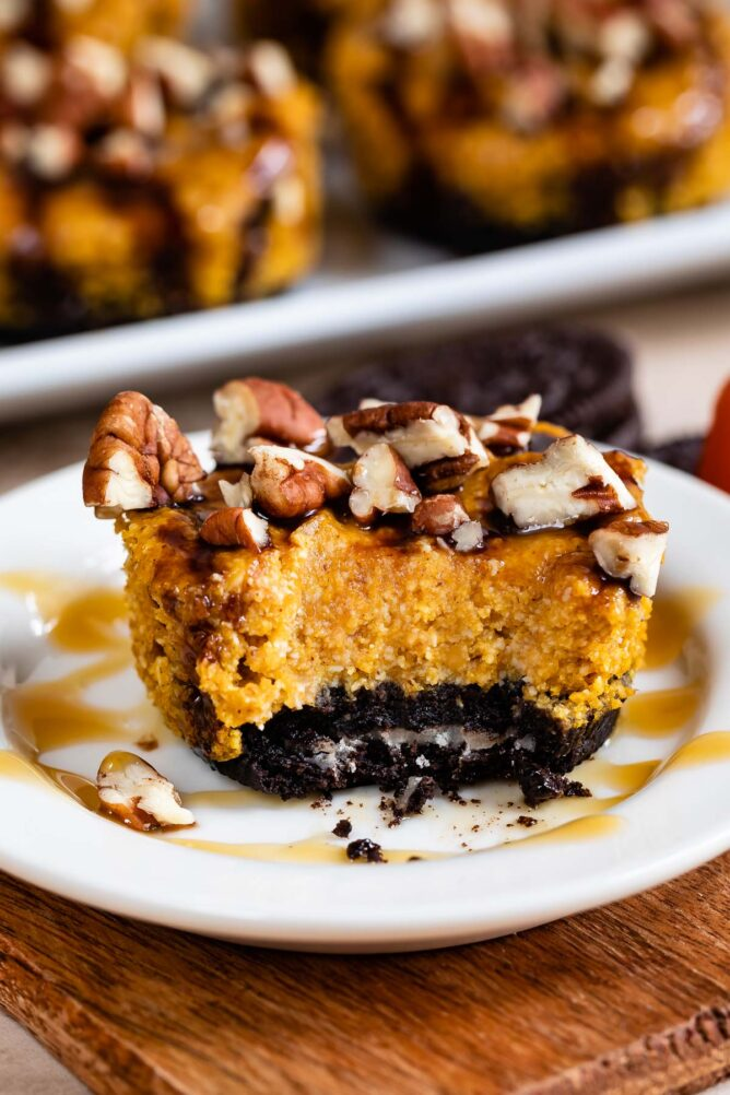 One mini turtle pumpkin cheesecake missing one bite with Oreo crust drizzled in caramel sauce