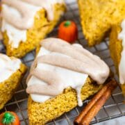 Pumpkin scones with icing on top surrounded by cinnamon sticks and pumpkin candies