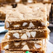 Stack of four pumpkin spice blondies with pumpkin candy and cinnamon stick and recipe title on top of image