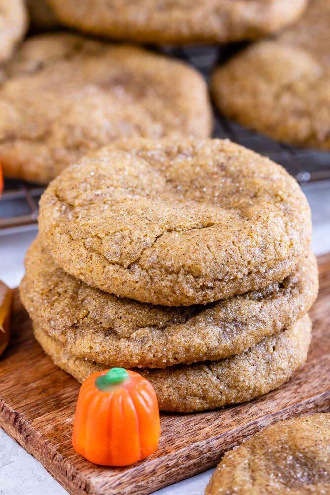 Three caramel stuffed pumpkin cookies with pumpkin candy next to them