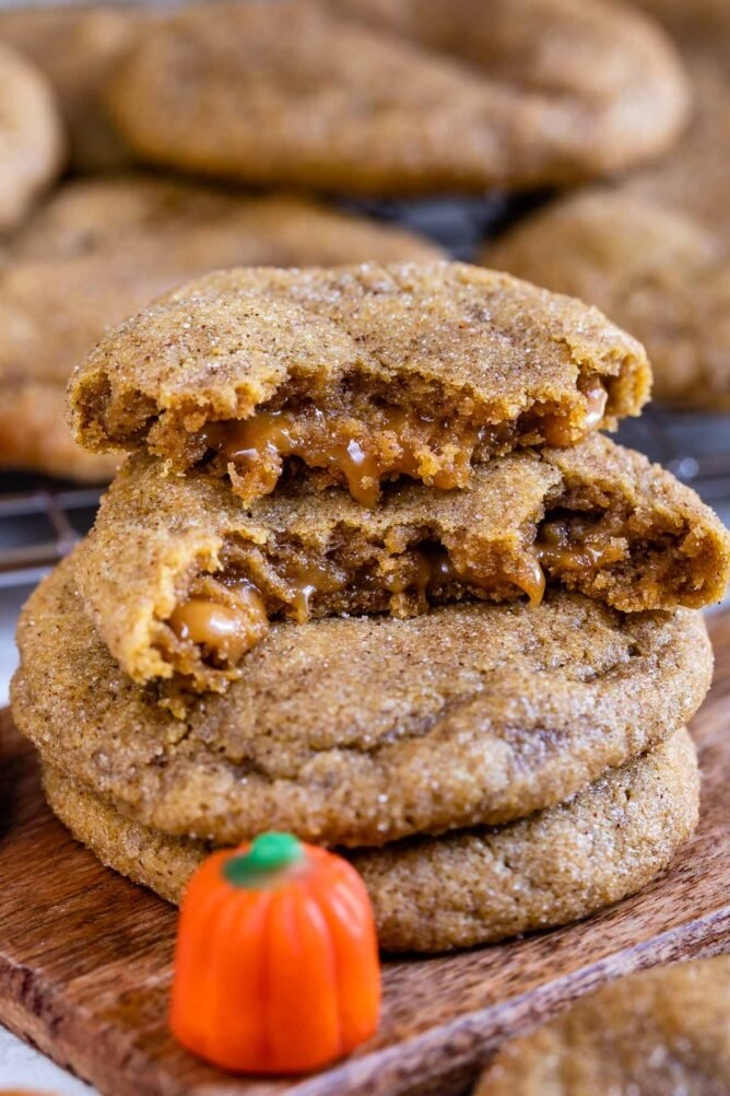 Caramel stuffed pumpkin cookies with top one cut in half to show inside caramel filling